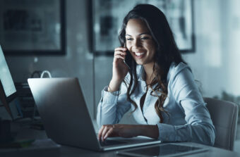 Woman-on-phone-using-laptop-in-home-office